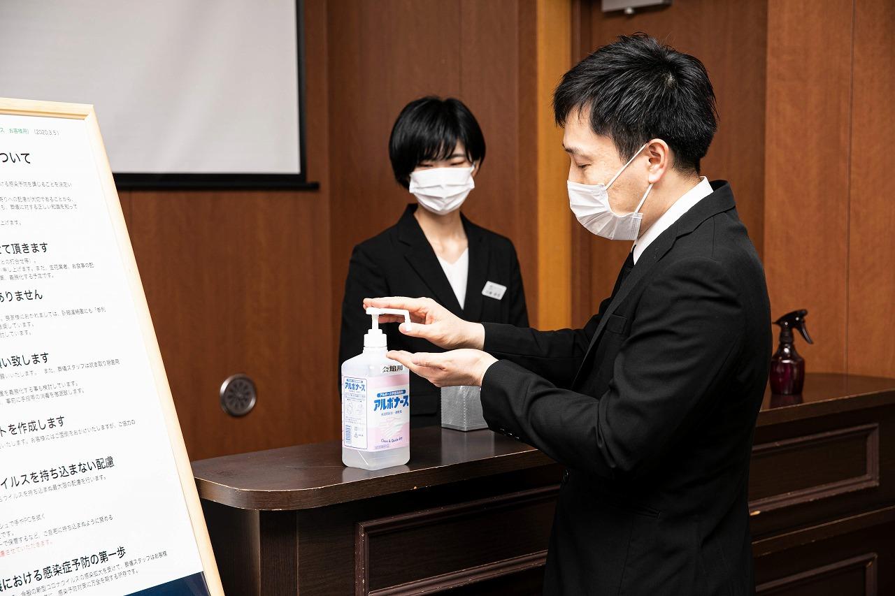 コロナ禍での葬儀における手指消毒等のイメージ画像。葬儀場スタッフがマスク着用・手指の消毒をするのはもちろん参列者にもマスク着用・手指の消毒を推奨する