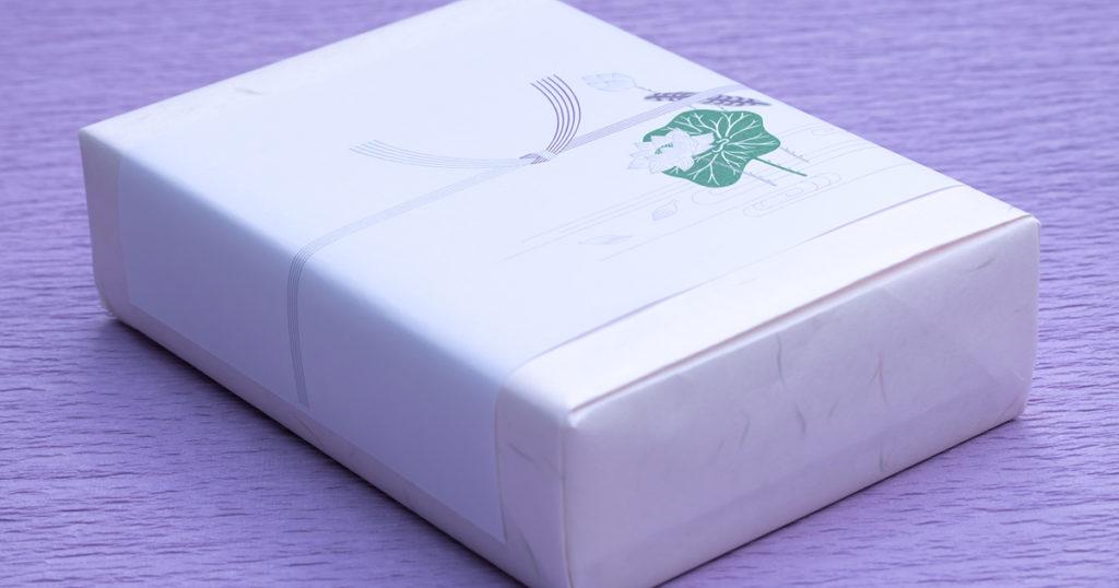 お供え物を包む包装紙は派手でないものを選び、弔事用の「熨斗(のし)」を付けます。四十九日までは白黒、四十九日以降は双銀の「結びきり」の水引のものを使用します。